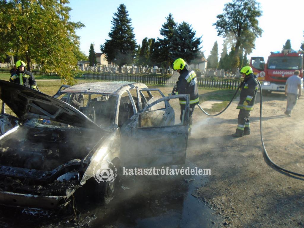 Teljesen kiégett autó, mellette tűzoltók, háttérben temető